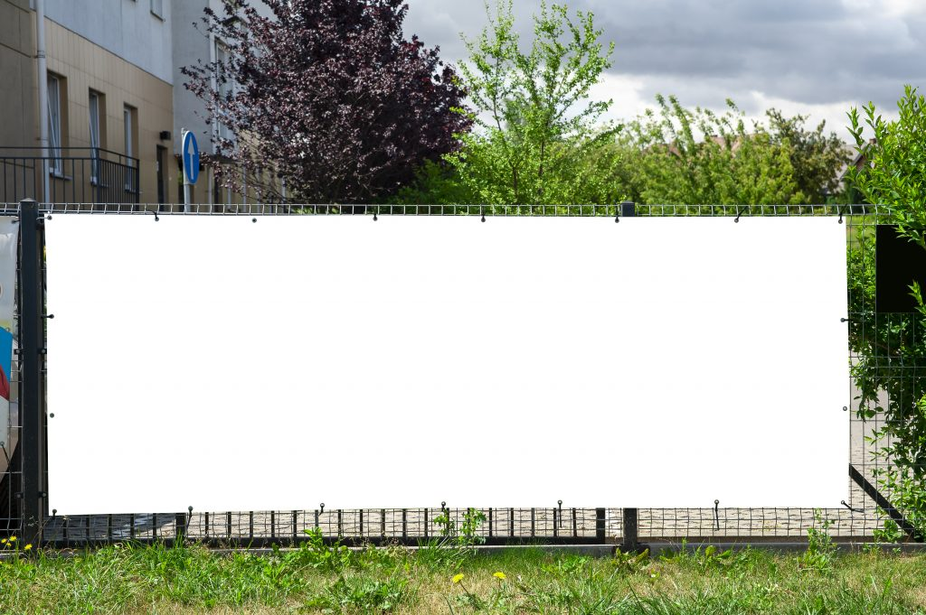 Blank Banner attached to a fence in an outdoor environment.